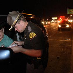 Utah Highway Patrol trooper Carlos Holley talks with LeRay Reese at the scene of a non-injury accident on I-15 on Thursday, Dec. 13, 2012.