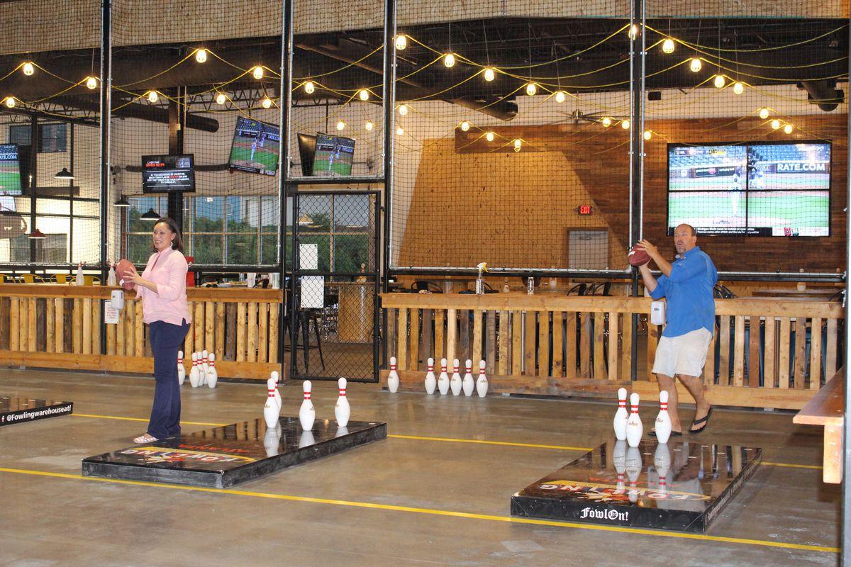 A man and woman throwing a football at bowling pins at the new Fowling Warehouse in Atlanta, GA