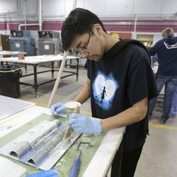 Orion Gonsalves applies epoxy to Fiberglas  material during a composites class at Davis Technical College in Kaysville on Wednesday, Jan. 29, 2020.