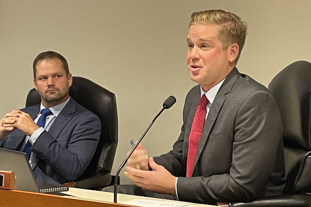 Republican state Rep. Andrew Beeler speaks in front of a microphoine in a committee room while Republican Rep. Bryran Posthumus.