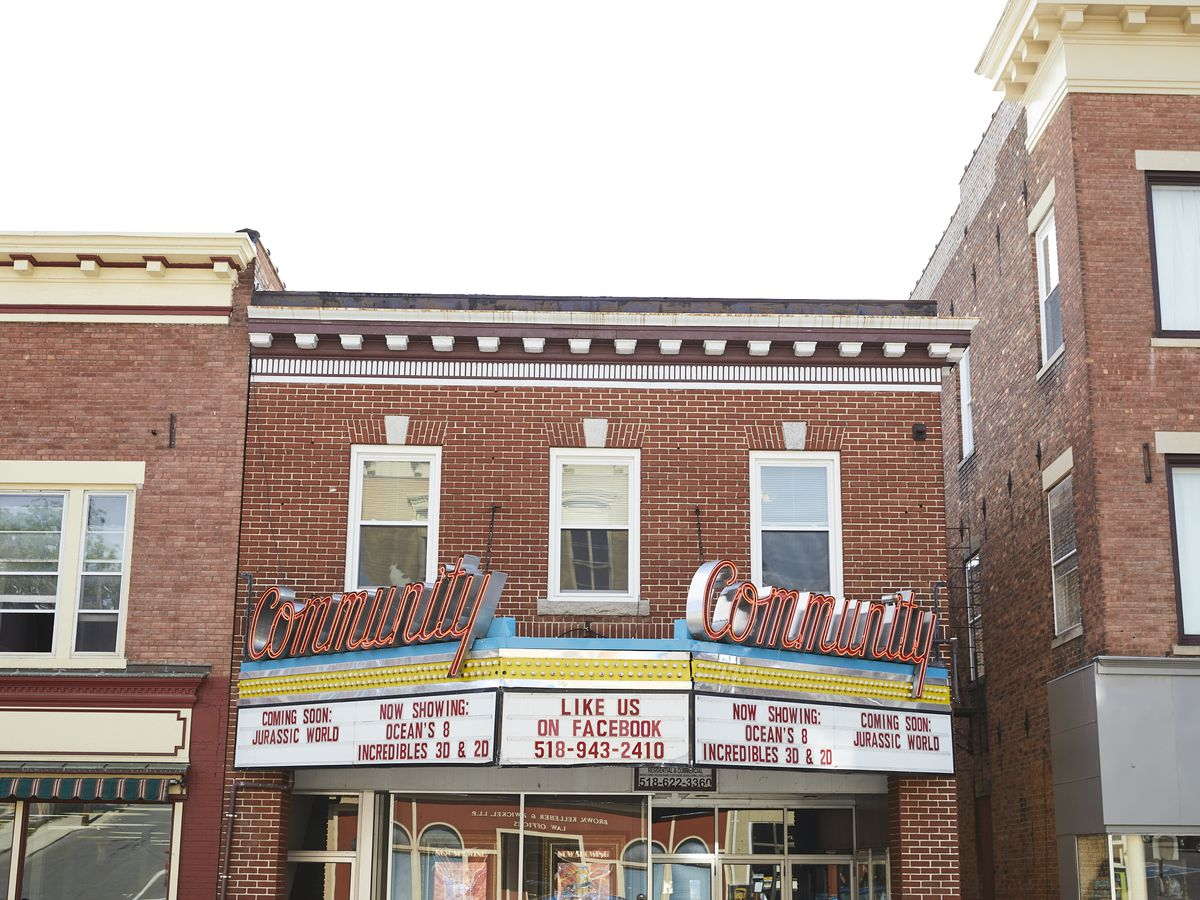 The exterior of a theater. There is a theater marquee with the names of various films on it. The facade of the theater is red brick.