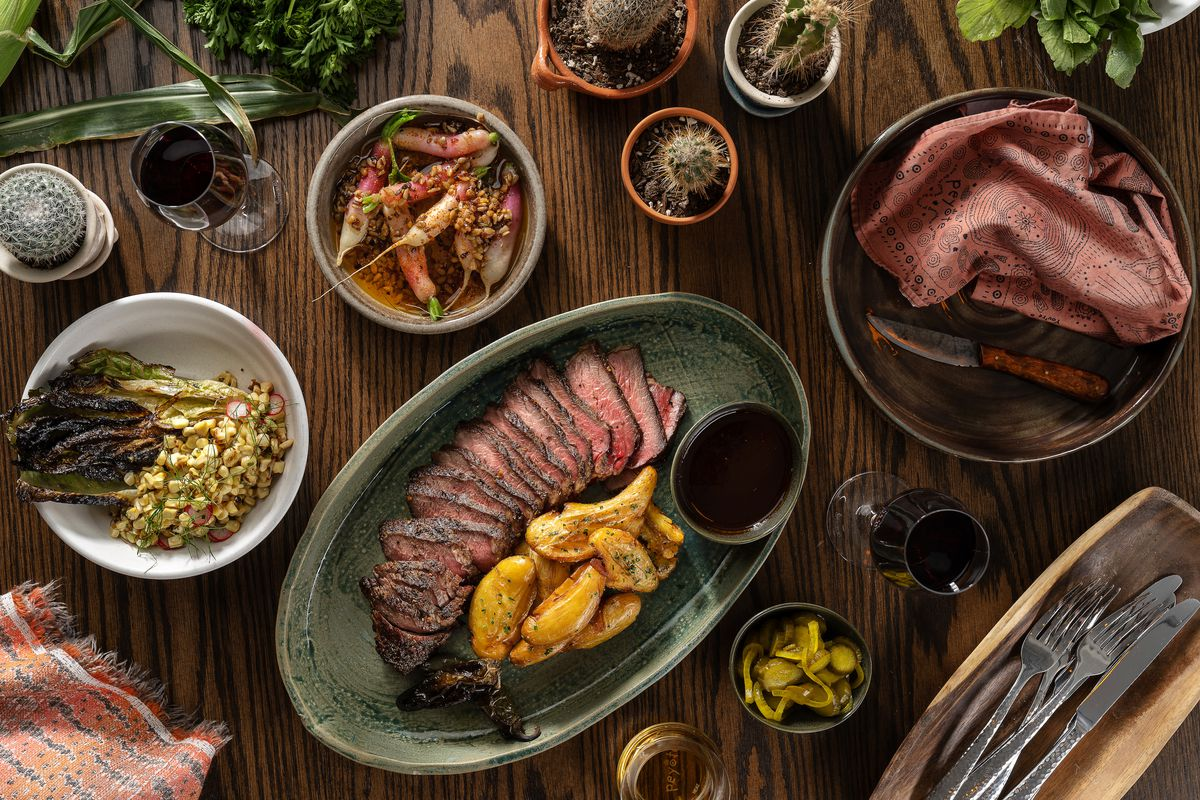 A spread with a tri-tip steak on a wood table.