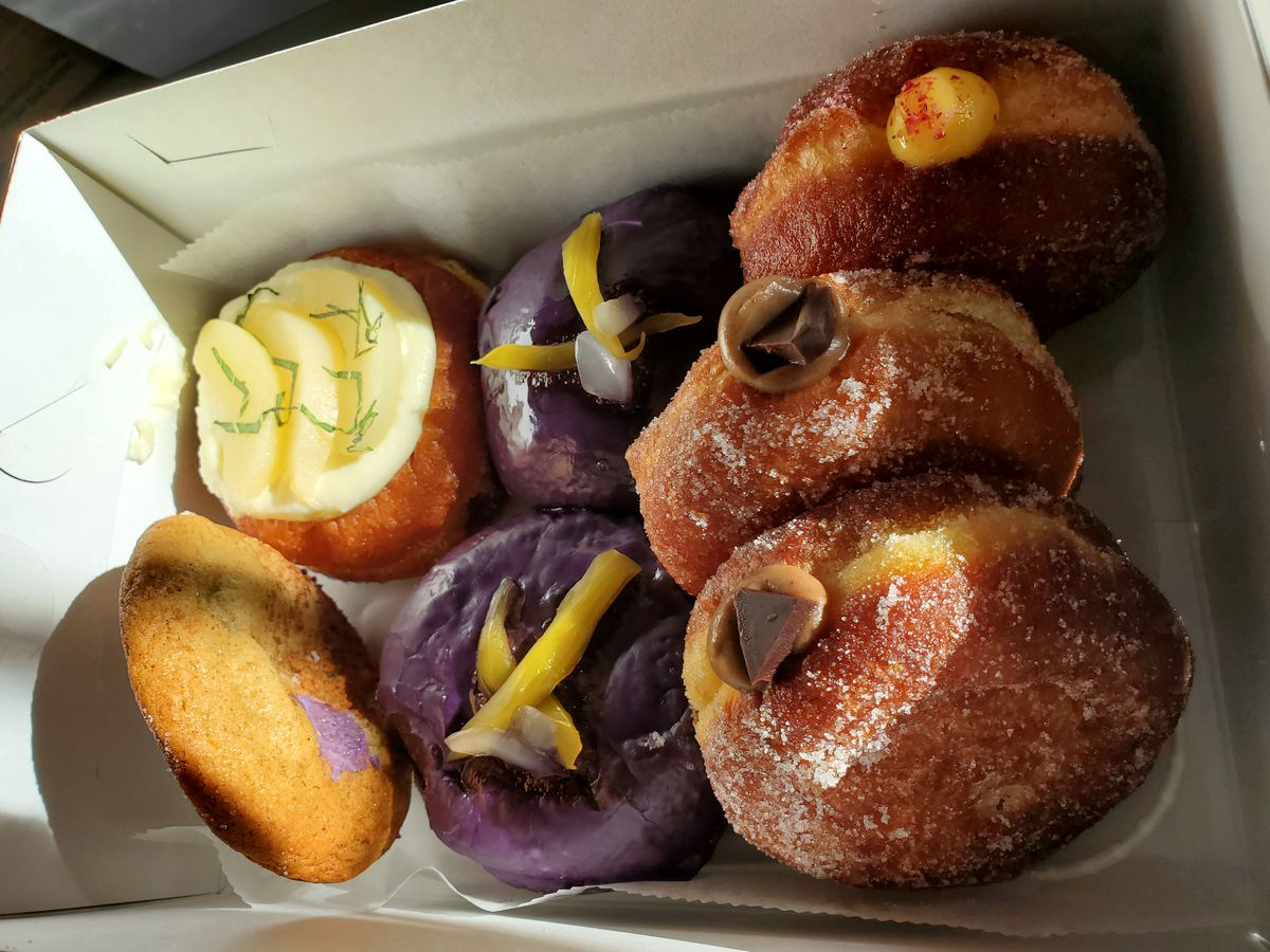 Treats from Rose Ave. Bakery include (clockwise from bottom right) Vietnamese coffee cream doughnuts, halo halo ube doughnuts with coconut cream, Saigon cinnamon and banana cookies, a white peach and miso doughnut, and a passion fruit guava doughnut.