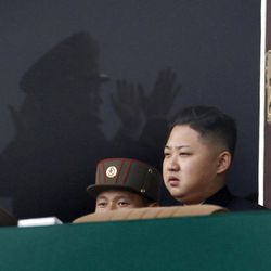 North Korean leader Kim Jong Un, walks past reflections of North Korean military officers clapping in a stadium in Pyongyang during a mass meeting called by the Central Committee of North Korea's ruling party on Saturday April 14, 2012. North Korea will mark the 100-year birth anniversary of the late leader Kim Il Sung on Sunday April 15. (AP Photo/Ng Han Guan)