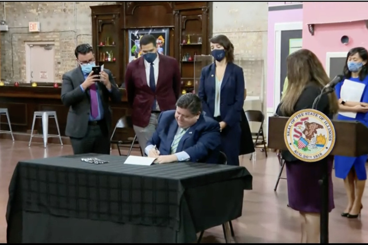 Gov. J.B. Pritzker signs a bill Monday after announcing funds to help the state's struggling renters and homeowners.