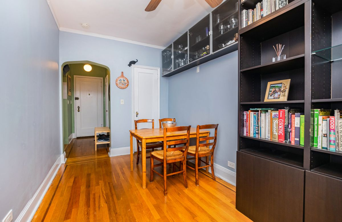 A nook with a wood dining table, hardwood floors, blue walls, a wooden bookshelf, and an arched entryway.
