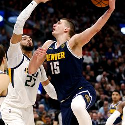 Denver Nuggets center Nikola Jokic (15) goes up and over Utah Jazz center Rudy Gobert (27) for a basket as the Utah Jazz and the Denver Nuggets play an NBA basketball game at Vivint Arena in Salt Lake City on Wednesday, Feb. 5, 2020. Denver won 98-95, giving the Jazz their fifth straight loss.