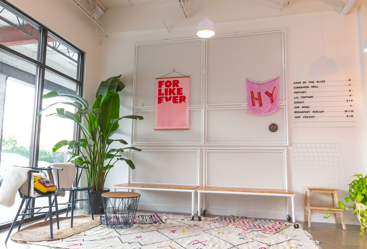 The seating area of the bakery with a white throw rug, potted plant, and menu