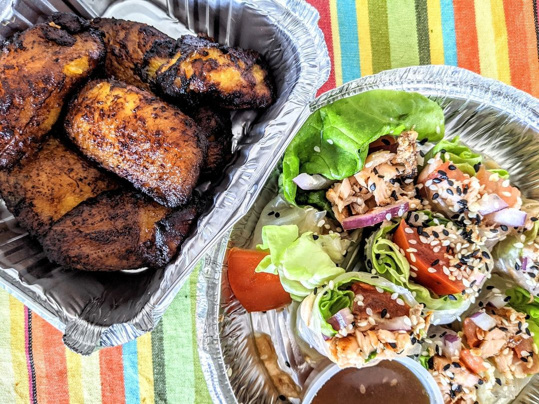 Overhead view of two takeout containers on a colorful striped tablecloth. One container is full of plantains, while the other has fresh rolls stuffed with salmon.