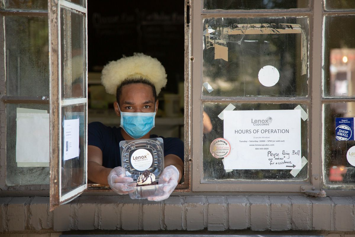 A person wearing a blue surgical mask and gloves with blonde hair and in a black tee shirt handing cupcakes through the to-go window