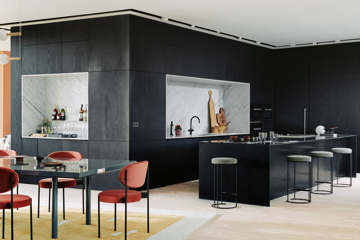 Black-walled kitchen with large island and sleek stools.