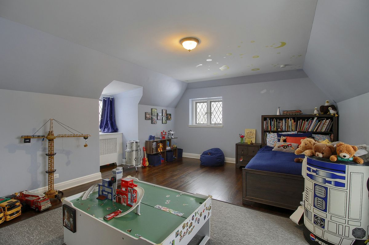 A room with a small twin sized bed and several kinds of kids toys, including legos and an R2D2 doll.