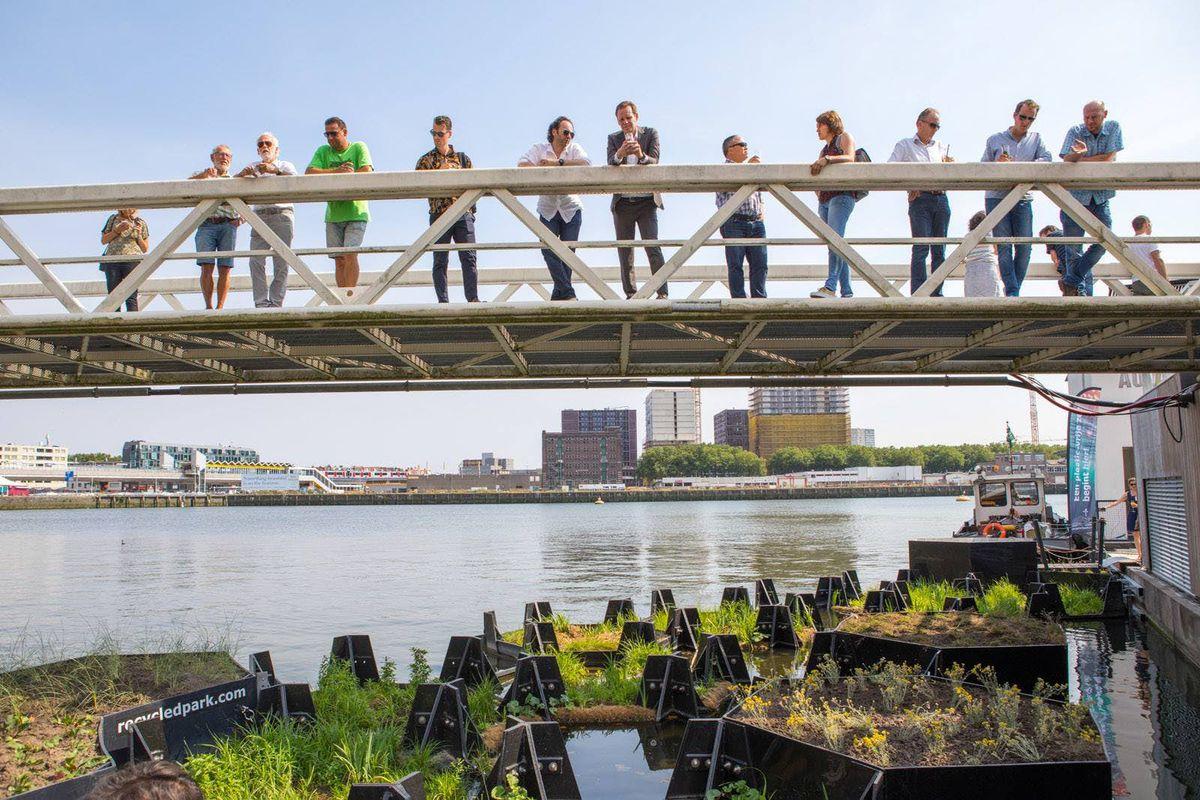 People on bridge overlooking floating hexagon park
