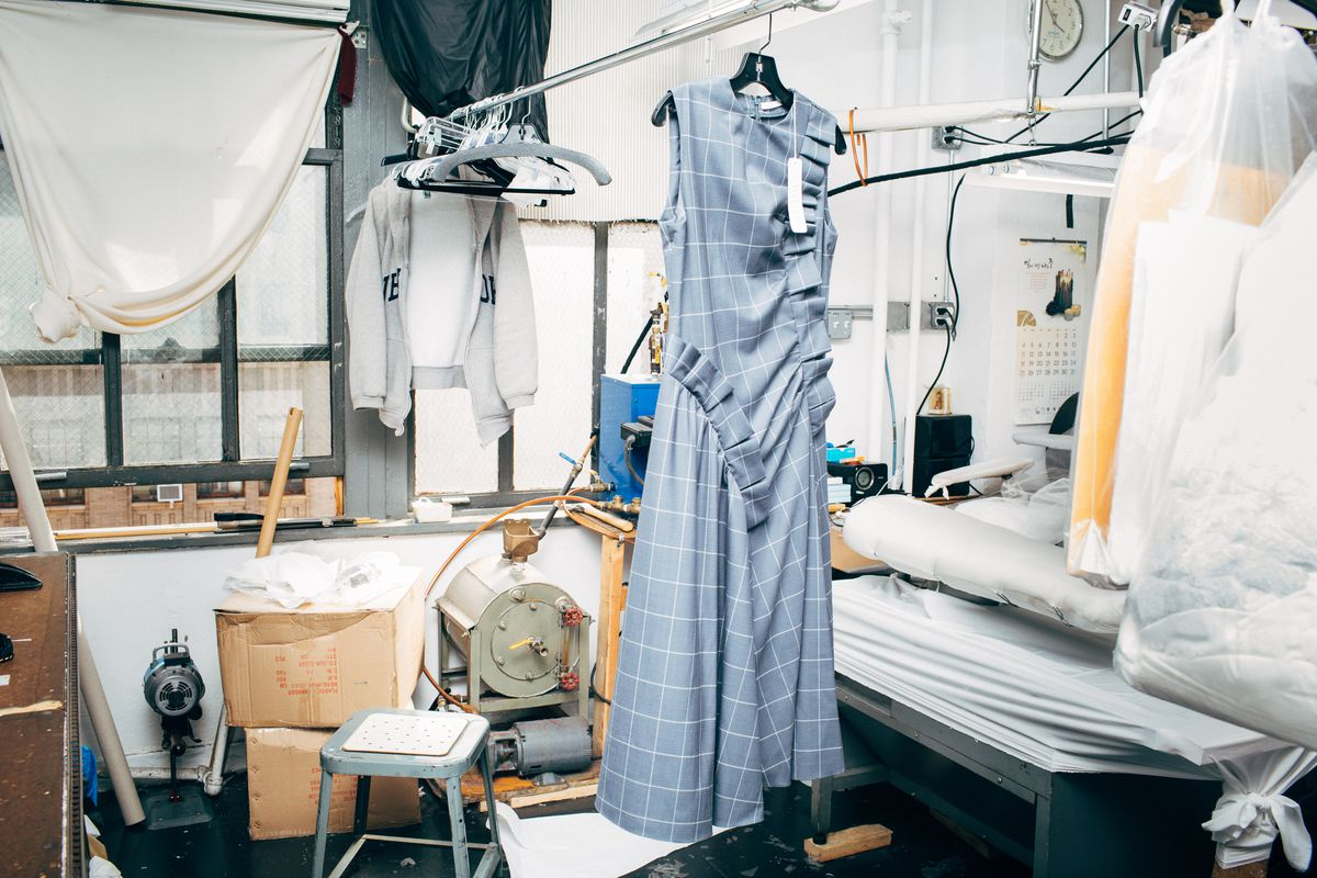 A blue dress with two ruffles running up the side hangs next to a work table.