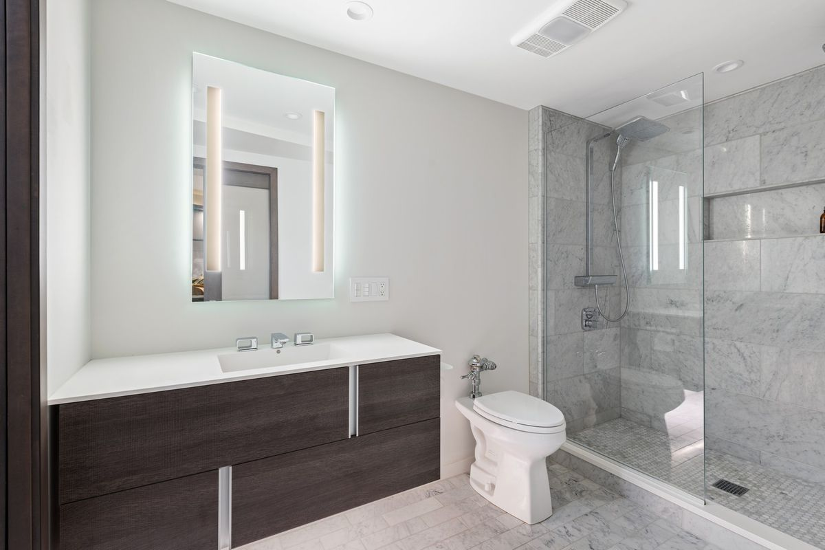 A bathroom with a floating vanity, rear-lit floating mirror, and marble lined shower with glass door.
