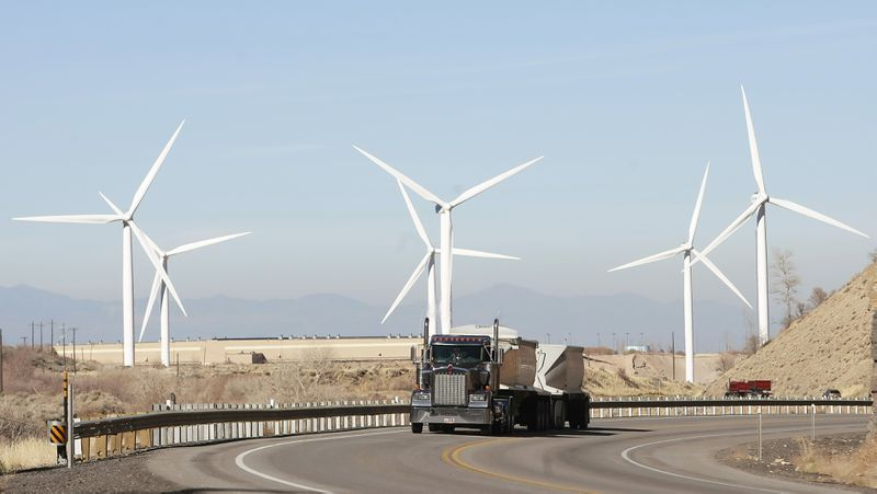 A coal truck drives past wind powered turbines in Spanish Fork, Utah