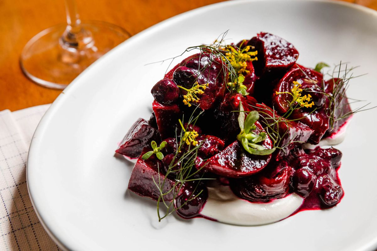 A white plate with roasted beets covered in herbs.