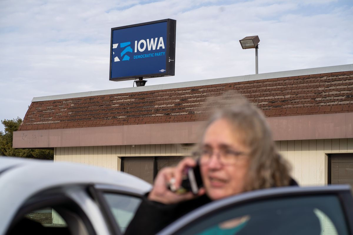 A woman speaks on the phone outside of the Iowa Democratic Party office