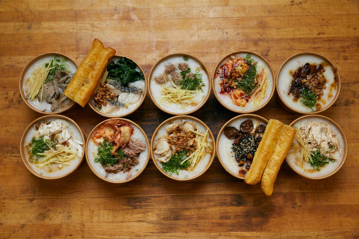 A top-down view of 10 congee dishes, with a variety of toppings, against a wood table