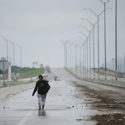 A survivor walks down the highway during Tropical Storm Harvey in Pearland, Texas, on Tuesday, Aug. 29, 2017.
