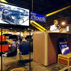 Rob Olson auctions off cars at the U.S. marshals auction Thursday. The marshals held an auction to sell off the $6 million worth of cars, boats and motorcycles of Jeffery Mowen, who is accused of operating a Ponzi scheme.