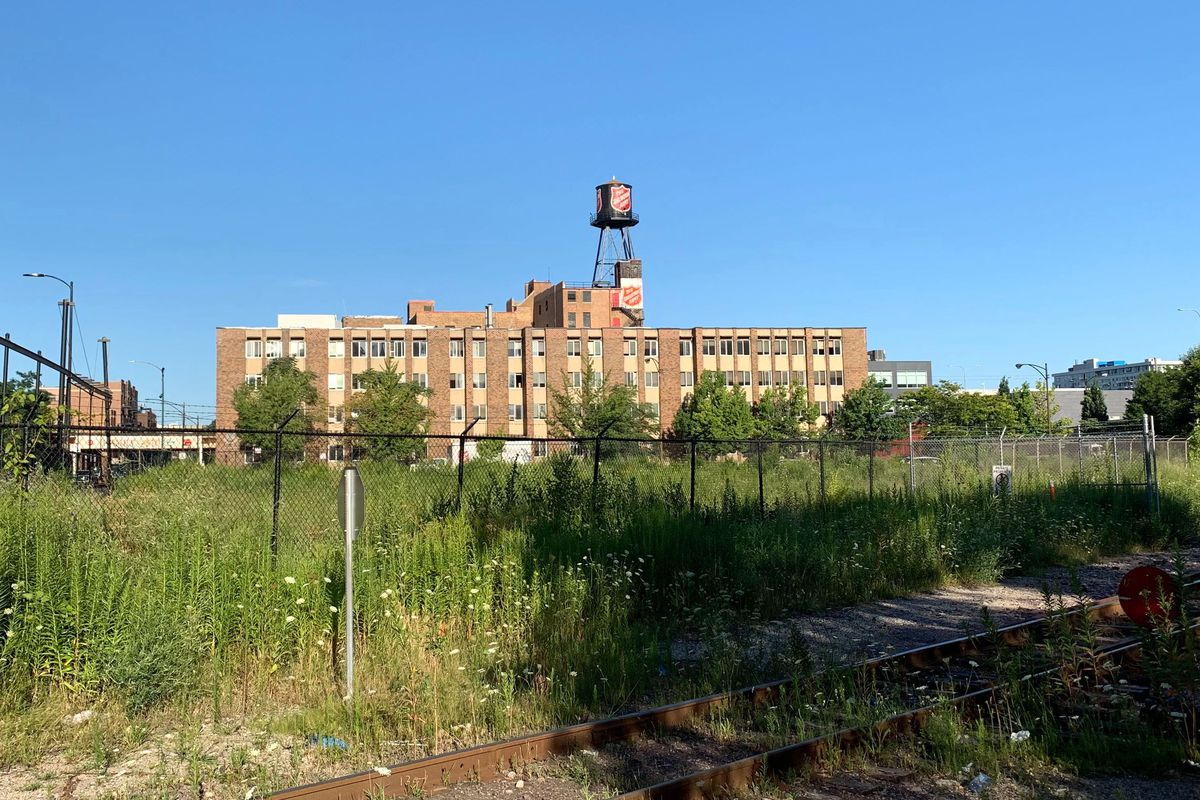 A brown and beige building topped by a Salvation Army sign and water tower. There is an overgrown vacant site and train tracks in the foreground.