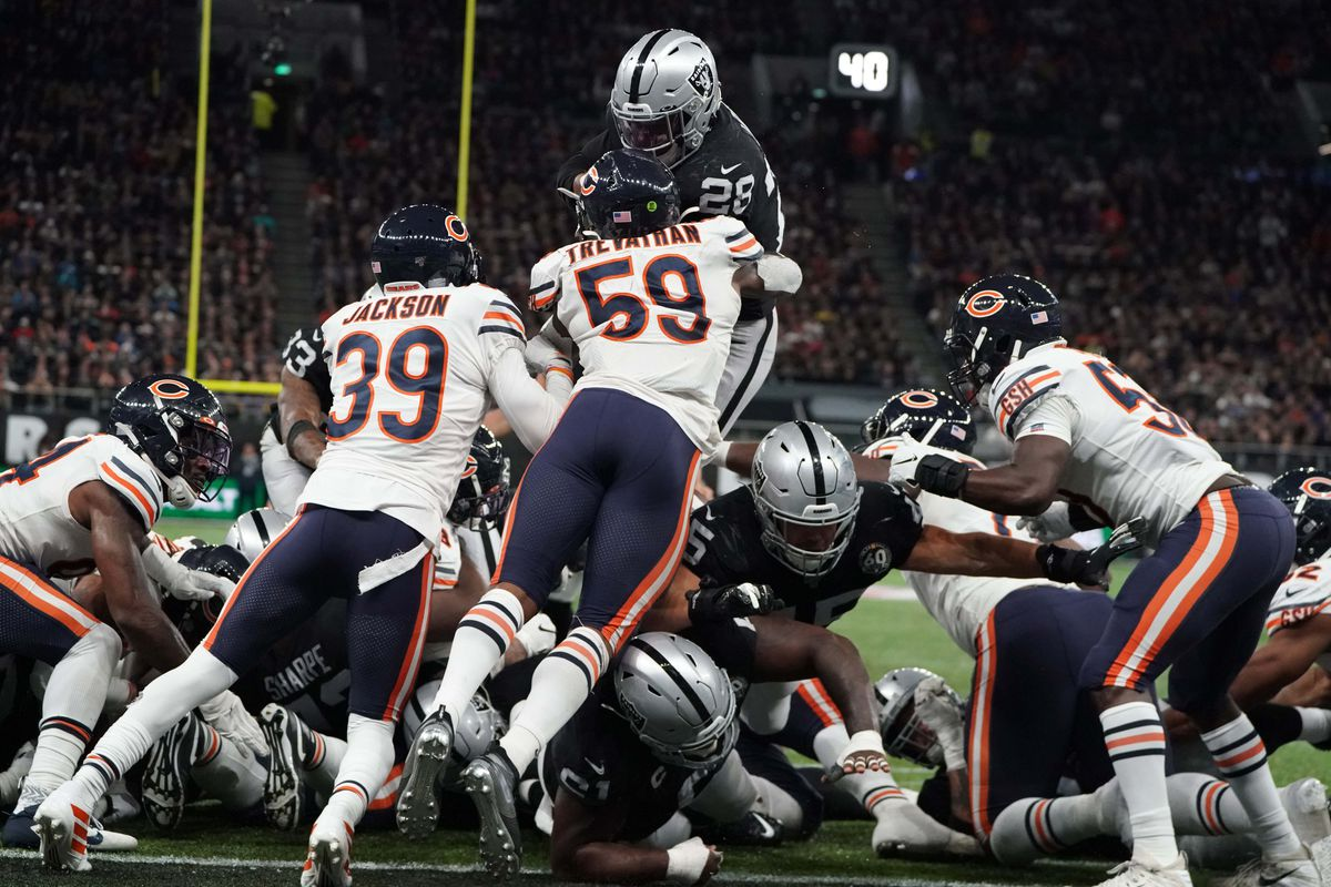 Raiders running back Josh Jacobs leaps into the end zone for a touchdown as Bears free safety Eddie Jackson and inside linebacker Danny Trevathan defend in the fourth quarter during an NFL International Series game at Tottenham Hotspur Stadium.