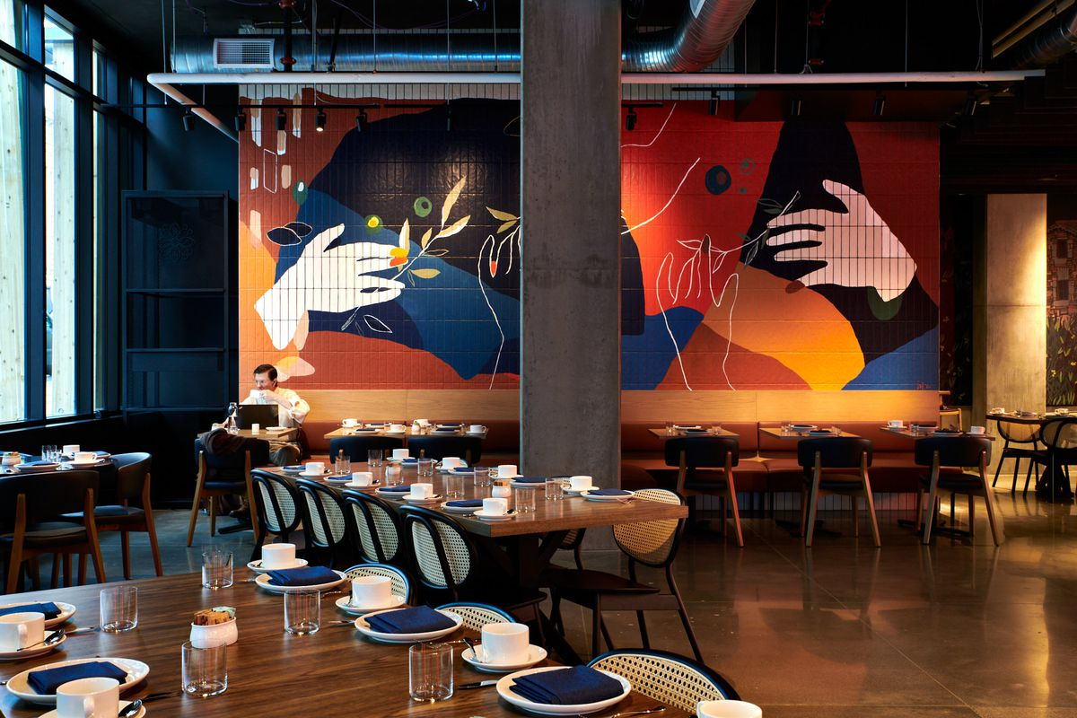 A concrete beam lies in the middle of the dining room, where large communal tables sit at angles in front of the large hand mural by Ivy Campbell