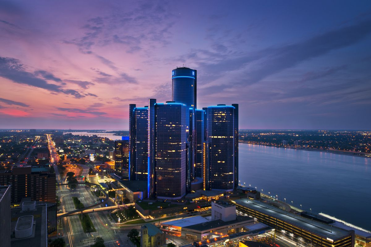 A photo of the Renaissance Center at twilight looking northeast up Jefferson Avenue. The sky is pink and blue.