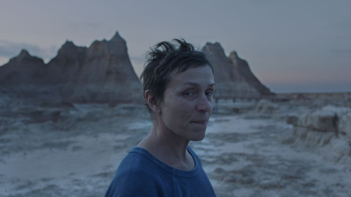 A woman stands against the backdrop of the Badlands, with a small smile on her face.