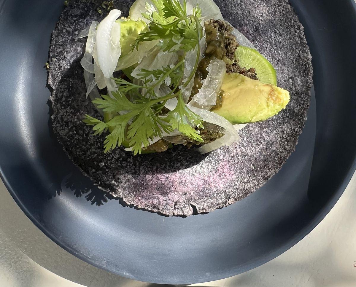 Vegan green chorizo sits atop a slice of avocado on an open-faced blue corn tortilla
