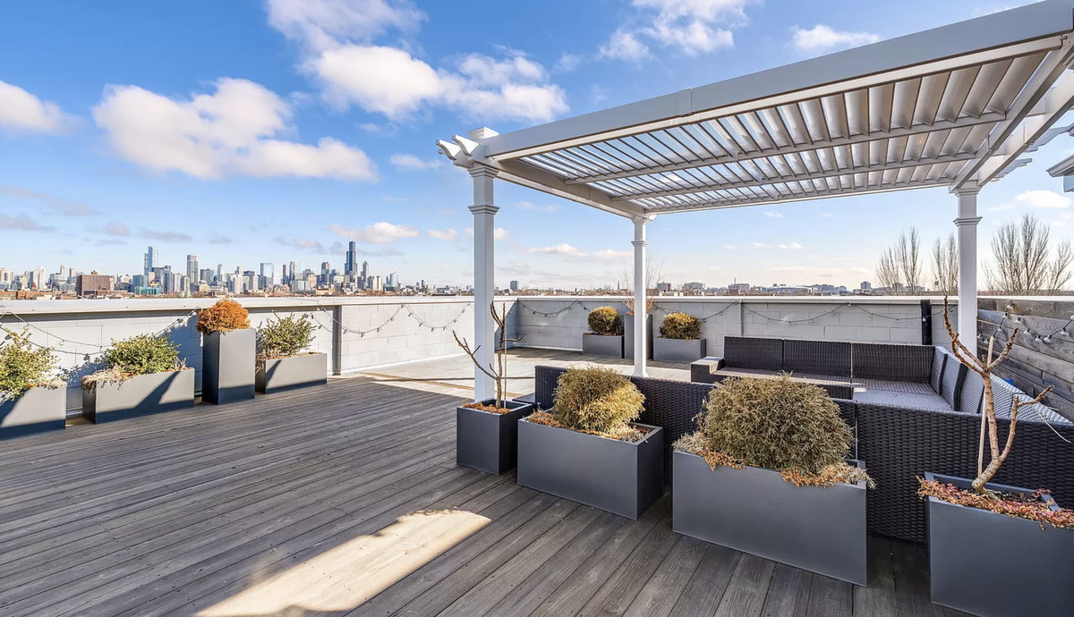 The rooftop deck has a pergola and sweeping views of the city.