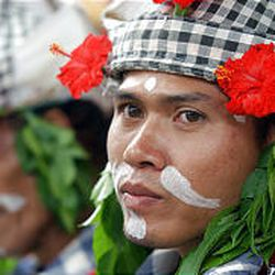 A Balinese man, dressed in traditional warrior costume, attends a cremation ceremony in Bali, Indonesia.