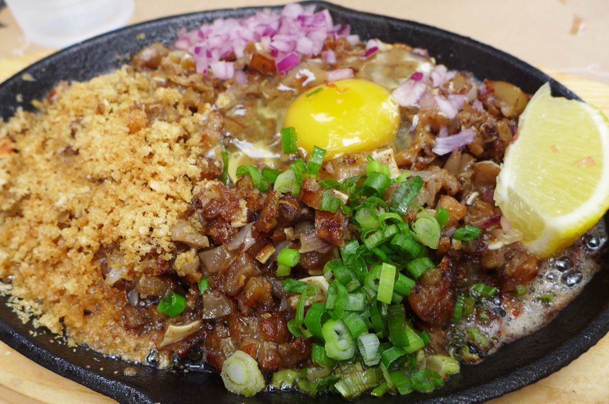 A black metal platter with minced pork parts and skin, plus a raw egg cracked on top.
