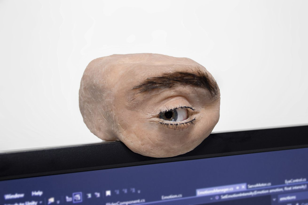 A hunk of synthetic flesh with an eyeball and eyebrow, plopped on top of a screen where a webcam would go. The eye is looking to the left.