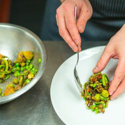 The roasted vegetables are plated atop the crème fraîche.