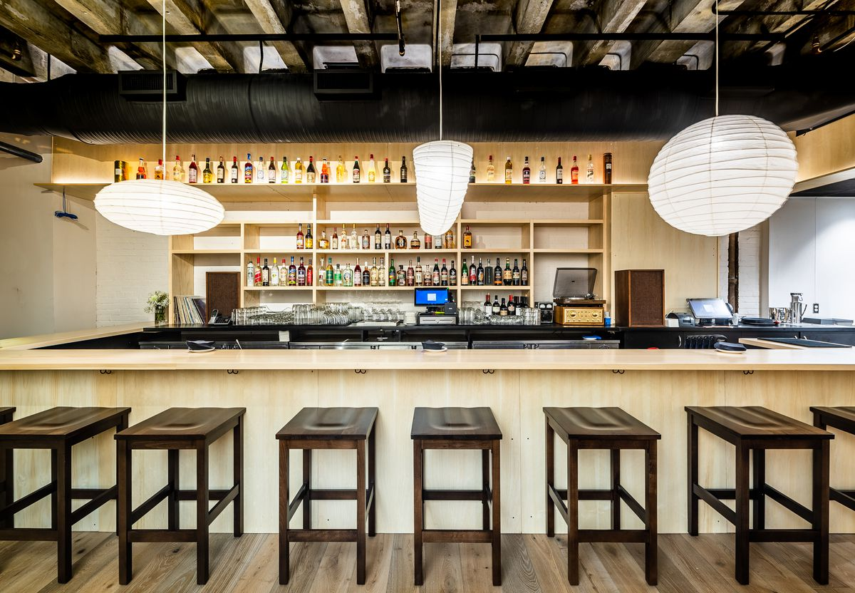 The downstairs bar at Tonari is covered in blonde wood and surrounded by spherical lanterns