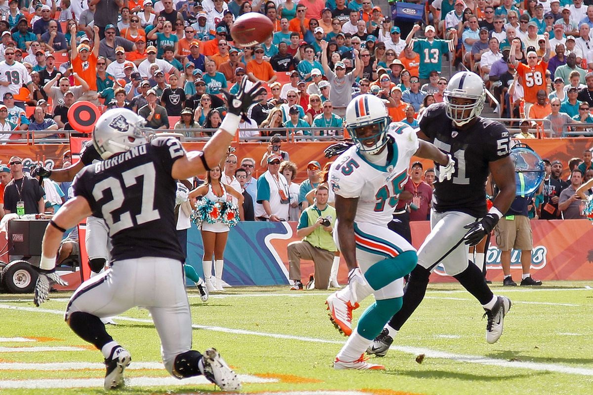 Davone Bess #15 of the Miami Dolphins and  Matt Giordano #27 of the Oakland Raiders fight for a loose ball