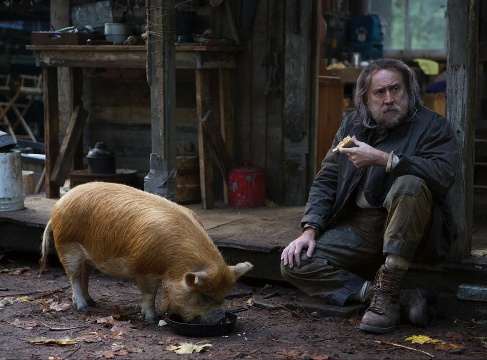 Nicolas Cage as Rob, the truffle-hunting hermit, eating breakfast with his prized pig in Pig.