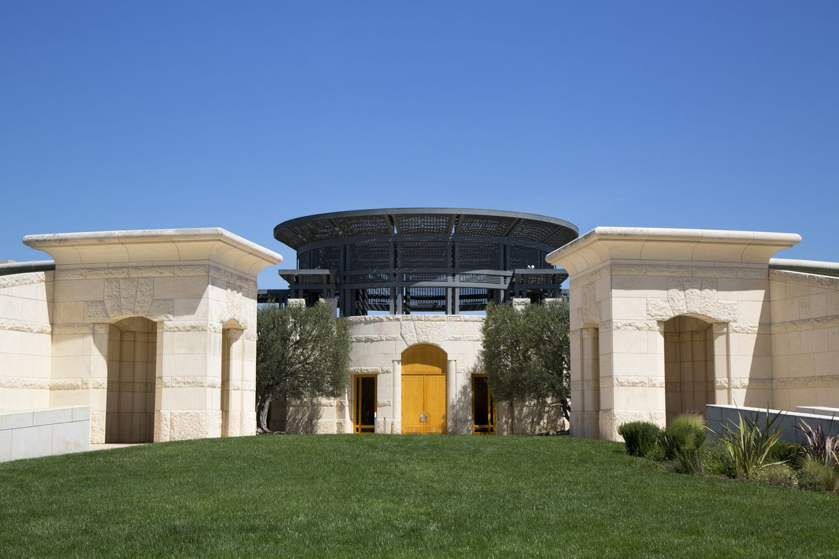 The exterior of Opus One Winery in California. There is a yellow door and the facade is white. There is a lawn in the foreground.