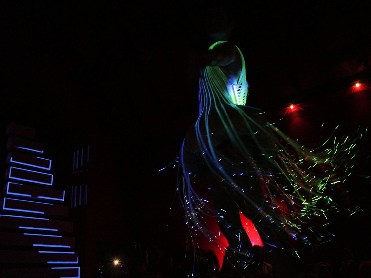 A woman in an LED dress takes a turn on the catwalk.