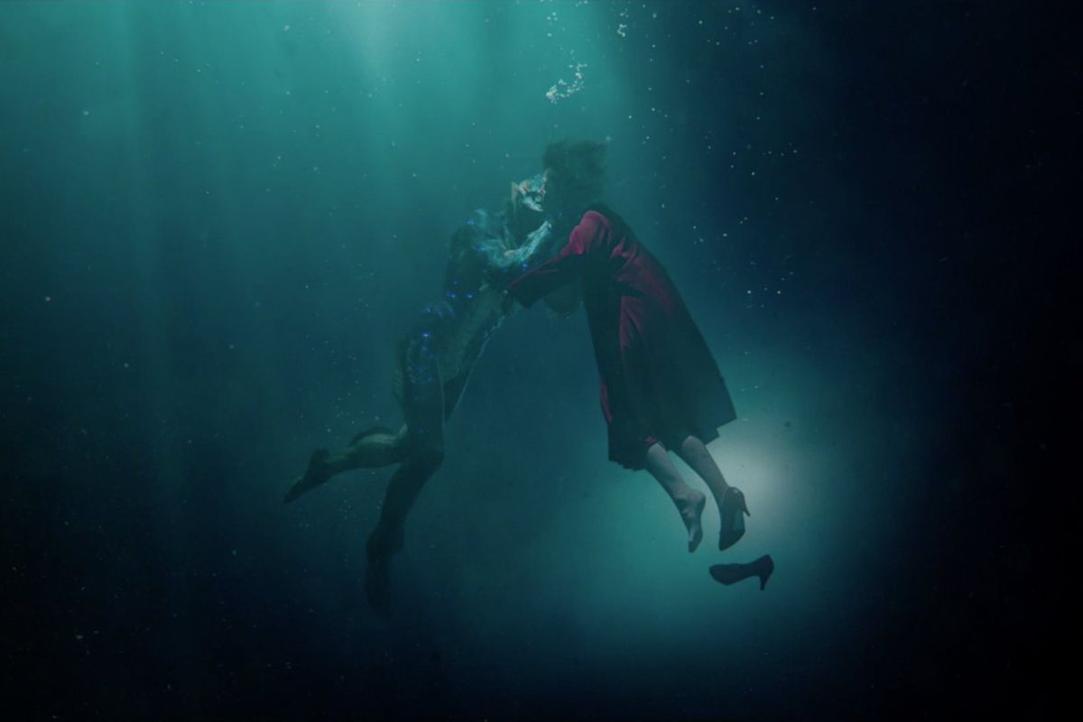 Screengrab of the movie The Shape of Water with a woman kissing the creature