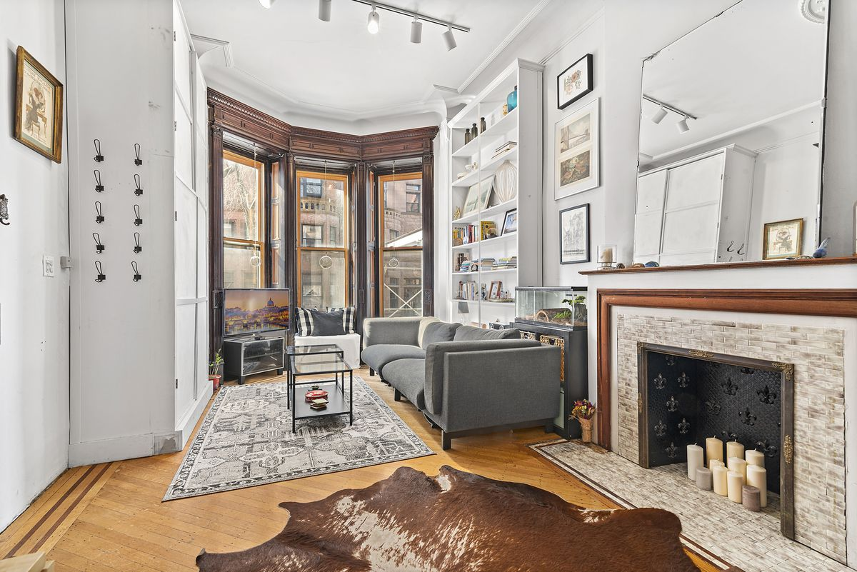 A living area with hardwood floors, a decorative fireplace, three large windows, a grey couch, and two rugs.