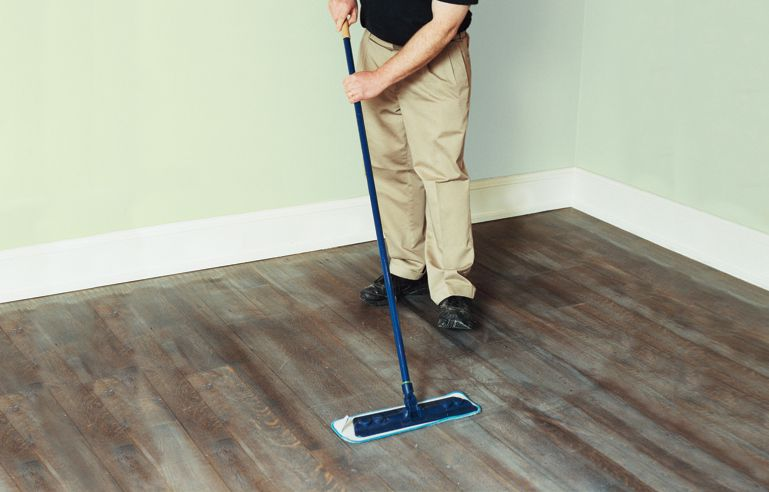 Man Dry-Tacking The Floor With Microfiber Cloth