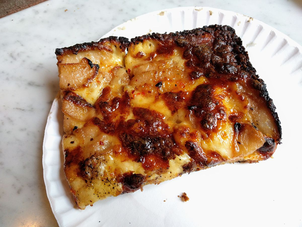 A square slice of pizza topped with pears