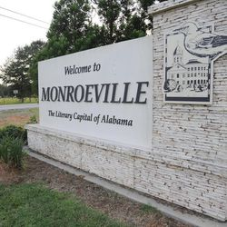 """This photo taken on Wednesday, July 8, 2015, shows a truck passing a sign decorated with a mockingbird in Monroeville, Ala., the hometown of """"To Kill a Mockingbird"""" author Harper Lee. Lee's second book """"Go Set a Watchman"""" is set for release July 14, 2015, and the town includes sites featured in both novels."""