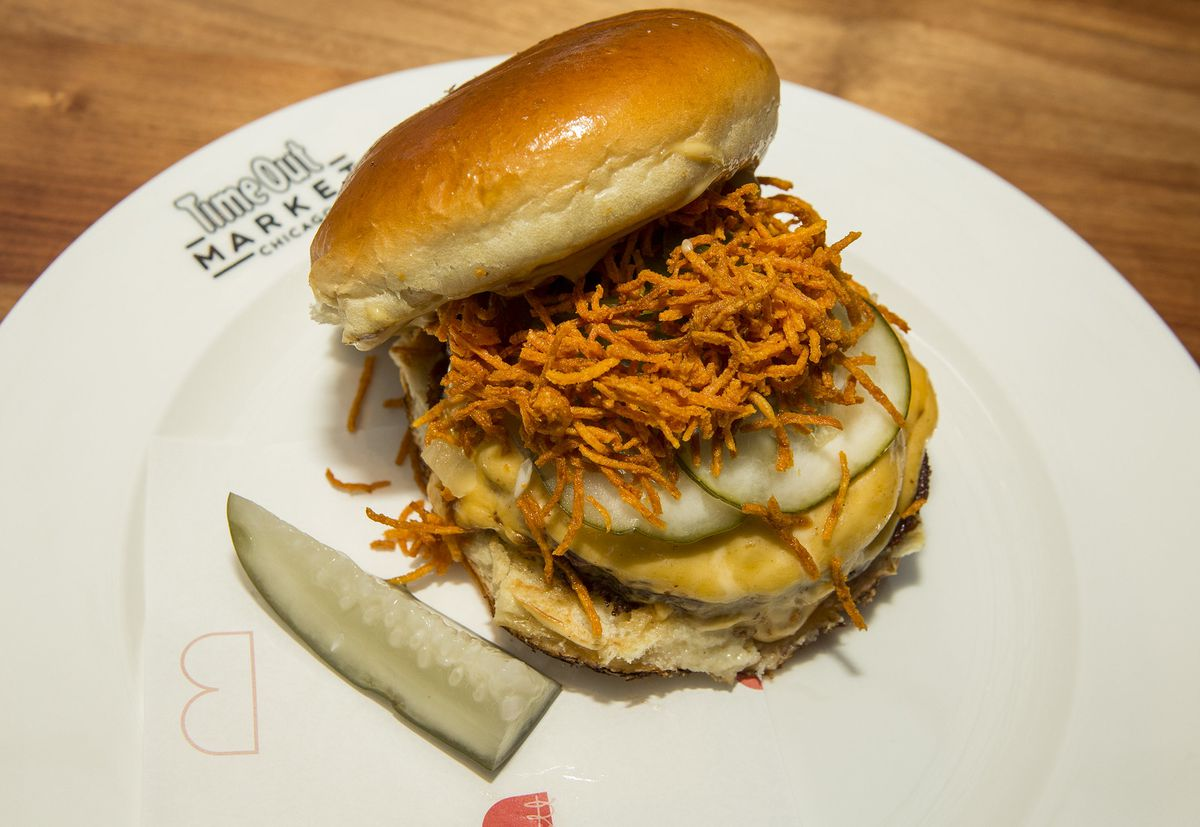 A burger with fried shoestrings and a pickle.
