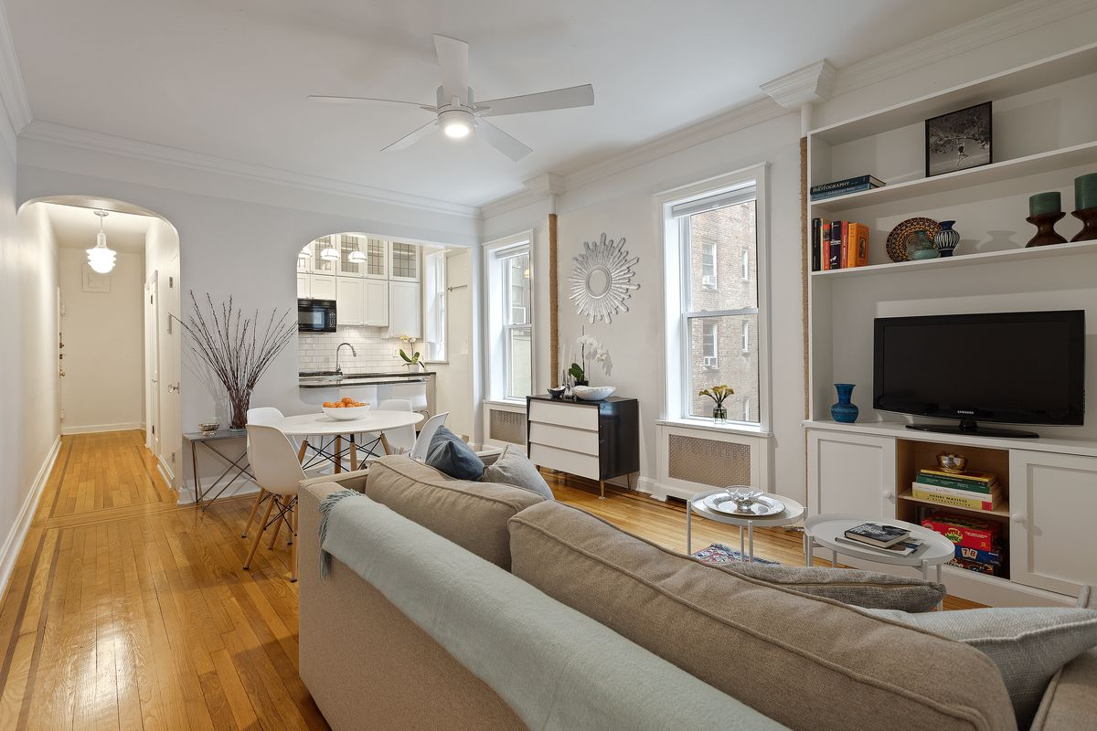 A living area with hardwood floors, two windows, a couch, two round coffee tables, and a TV.