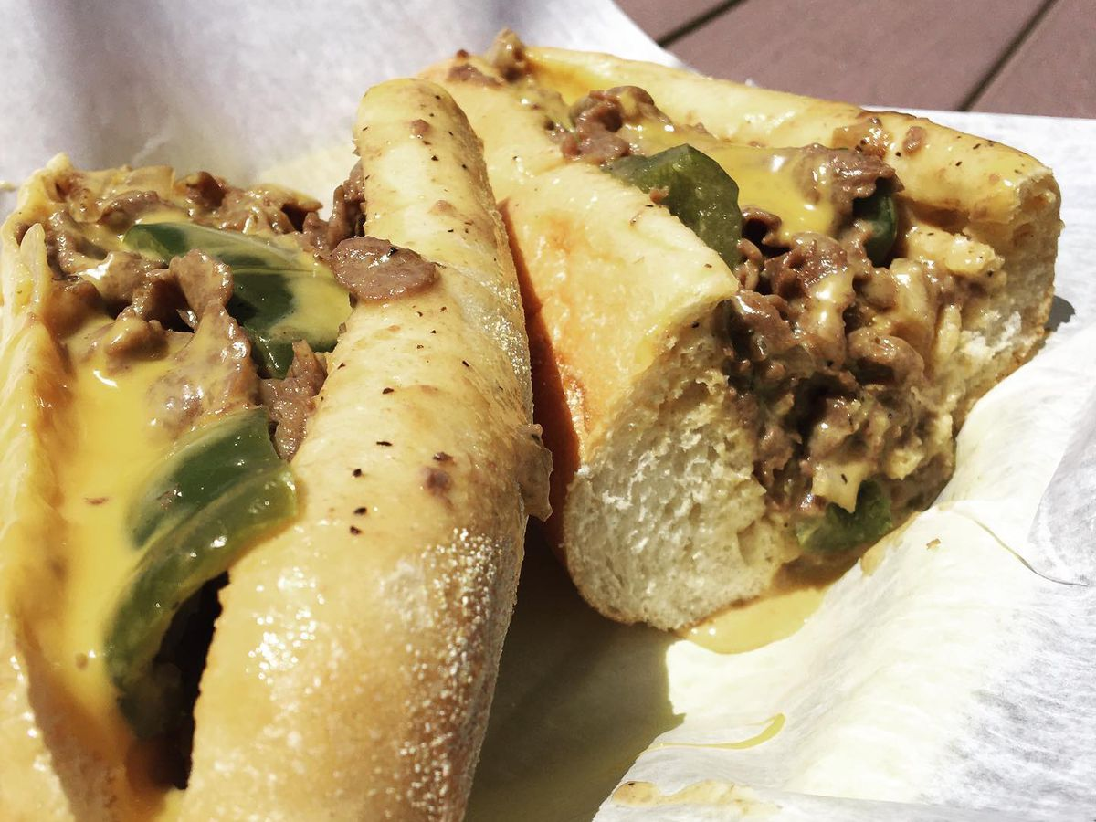 An extra cheesy cheesesteak in two halves sits on white paper