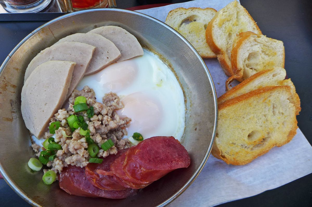 A metal vessel with three kinds of meat next to fried eggs, with toast on the side.